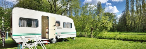 Fotografering White caravan trailer on a green lawn in a camping site