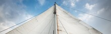 White Sails Of A Sloop Rigged Yacht Against Cloudy Blue Sky. Sailing And Rigging Equipment. Recreation Theme. North Sea, Norway