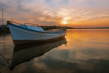 Colorful Sunset At The Ocean With Specular Reflection With Fisherman Boat