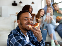Attractive Black Guy Eating Yummy Pizza, His Diverse Friends With Cellphone Having Fun On Background