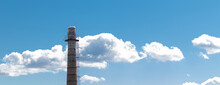 A Large Brick Chimney On A Background Of Blue Sky With Clouds