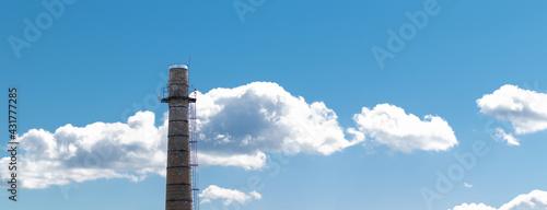 Fotografija A large brick chimney on a background of blue sky with clouds