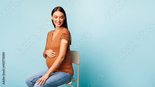 Pregnant Woman Vaccinated Against Coronavirus Sitting On Blue Background, Panorama