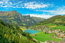 Valley Of Engelberg With Eugenisee Lake. View From Cable Car To Titlis Mountain Of The Uri Alps. Located In Cantons Of Obwalden And Bern, Switzerland, Europe. Summer Season, Clear Blue Sky.
