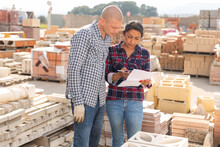 Woman Order Picker With Papers Collecting Products In The Warehouse Of Building Materials, Man Worker Helping Her