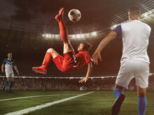 Soccer Striker In Red Uniform Hits The Ball With An Acrobatic Kick In The Air At The Stadium