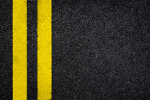 Top View Of Dark Wet Asphalt Road With Double Yellow Line. High Resolution Full Frame Textured Background Of Black Asphalt, Viewed From Above. Copy Space.