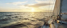 White Sailboat In An Open Sea At Sunset. Single Handed Sailing A 34 Ft Yacht. Close-up View Of The Deck, Mast And Sails. England, UK. Colorful Dramatic Cloudscape. Sport, Racing, Recreation