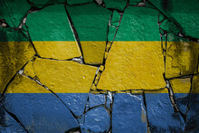 National Flag Of Gabon. Depicting In Paint Colors On An Old Stone Wall. Flag  Banner On Broken  Wall Background.