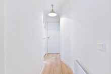 Interior Of Long Narrow Hallway With Wooden Floor And White Walls In Apartment Designed In Minimal Style