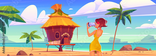 Fototapeta Girl take photo of landscape with bungalow, sea and palm trees. Vector cartoon illustration of woman photographs ocean beach with resort wooden house on mobile phone camera obraz