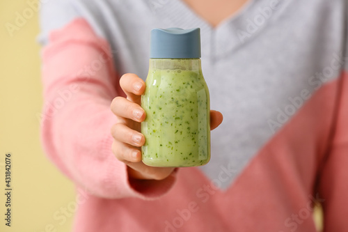 Obraz Woman with bottle of fruit smoothie on color background - fototapety do salonu