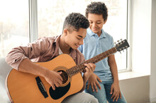Teenage Boy With His Little Brother Playing Guitar At Home