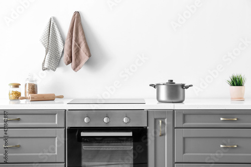 Fototapeta Modern furniture with oven near white wall in kitchen obraz