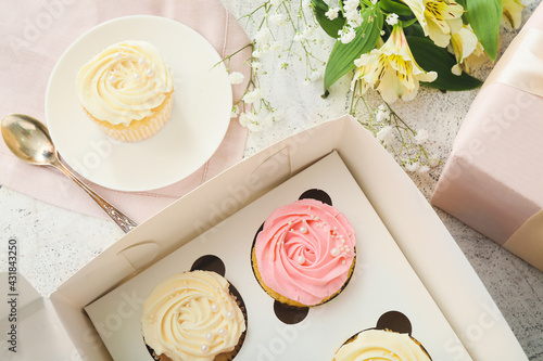 Fototapeta Composition with tasty cupcakes and flowers on light background, closeup obraz