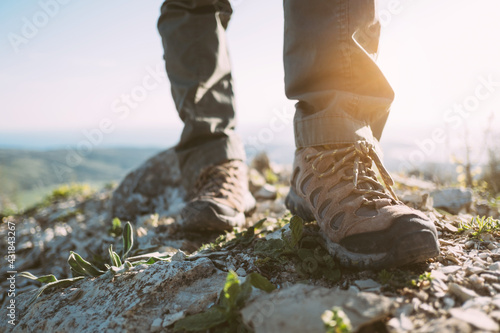 View of the feet of a traveler in trekking boots on the top of the mountain. - fototapety na wymiar