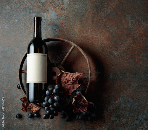 Obraz Bottle of red wine with grapes and dried vine leaves on an old rusty background. - fototapety do salonu