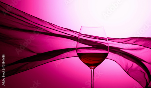 Obraz Glass of red wine on a background of waving curtain. - fototapety do salonu