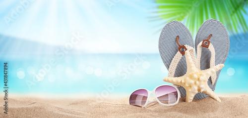 Fototapeta Flip flops on sunny sea beach with copy space obraz