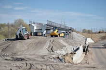 Construction Equipment Forms An Artificial Embankment And Compresses The Ground Against The Background Of The Construction Of A New Bridge.