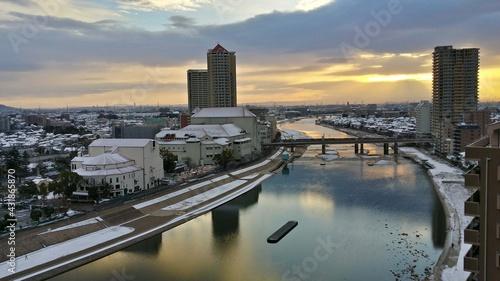 Fotografering 雪の中の宝塚劇場と川の夕焼け風景ワイド撮影