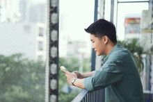 Happy Man Using Mobile Phone At Balcony