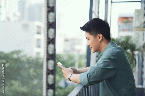 Obraz na plátně Happy man using mobile phone at balcony