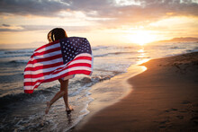 Cheerful Happy Woman Outdoors On The Beach Holding USA Flag Having Fun.