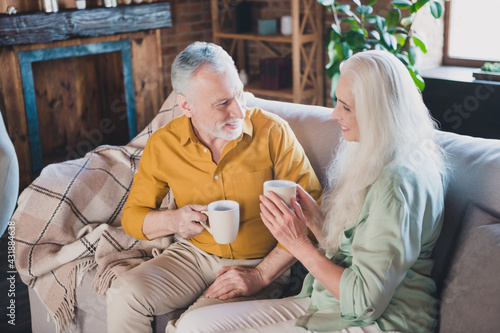 Obraz Photo of positive charming man and woman old people good mood sit sofa drink tea indoors inside house home - fototapety do salonu