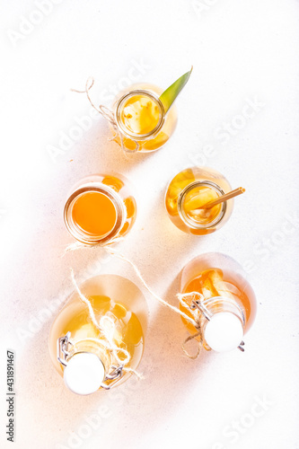 Obraz Homemade Fermented Raw Kombucha Drinks In Bottles. Gray Table Background. Top view - fototapety do salonu