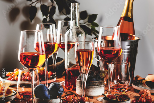 Obraz Pink rose wine glasses and bottles on table served for summer festive dinner party with different kinds of appetizers - fototapety do salonu