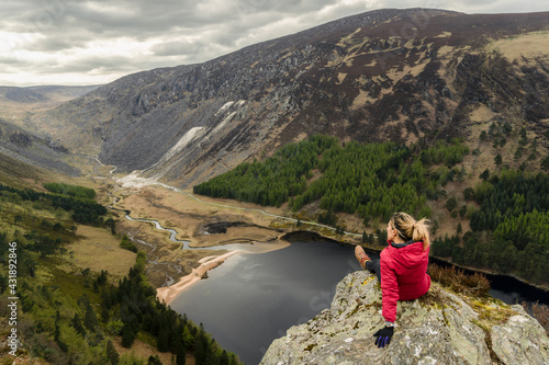 Fototapeta Woman traveler in a red jacket in the Spink Viewing Spot in Wicklow mountains national park, Ireland obraz
