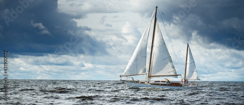 Old expensive vintage wooden sailboat (yawl) close-up, sailing in an open sea. Dramatic cloudscape. Coast of Maine, US - fototapety na wymiar