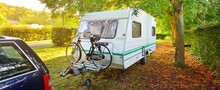 Caravan Trailer With A Bicycle And A Car Parked On A Green Lawn Under The Trees In A Camping Site. Normandy, France. Vacations, Leisure Activity, Recreation, Tourism, Road Trip, Travel Destinations