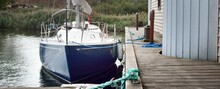 Blue Sloop Rigged Yacht Moored To A Wooden Pier In A Small Village, Close-up. Firewood In The Background. Norway