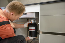 The Worker Is Installing A Household Waste Shredder For The Kitchen Sink.
