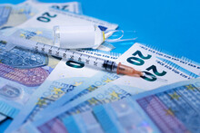 Syringe To Take Advantage Of The Coronavirus Vaccine, The Flu Vaccine On Money In 20 Euro Bills. Next To The Vaccine Vial Part Of The Vial Syringe And Banknotes Are Out Of Focus On A Blue Surface.