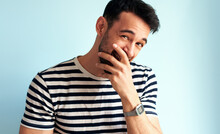 Happy Young Man Laughing, Covers His Mouth With Hand, Looking To The Camera, Posing For Advertisement, Isolated On Blue Background. Handsome Male Has Joyful Expression, Posing Against White Blue Wall.