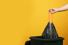 Man Throwing Garbage Bag Into Bin On Yellow Background, Closeup. Space For Text