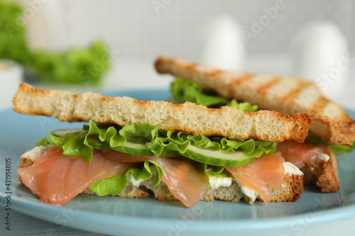 Tasty sandwiches with salmon on blue plate, closeup