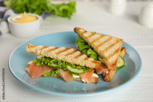 Blue plate with tasty sandwiches on white table