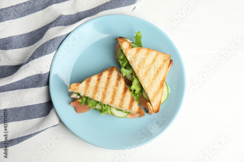 Blue plate with tasty sandwiches on white table, top view