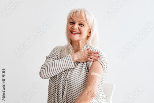 Fototapeta Smiling Mature Woman Showing Vaccinated Arm After Antiviral Injection obraz