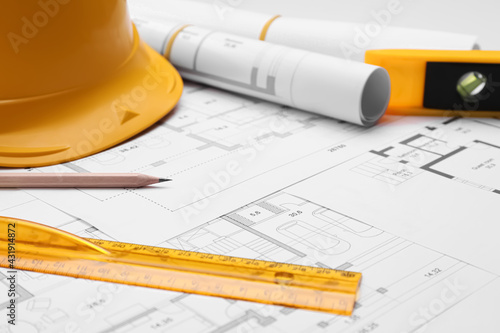 Pencil, ruler and hardhat on blueprints, closeup