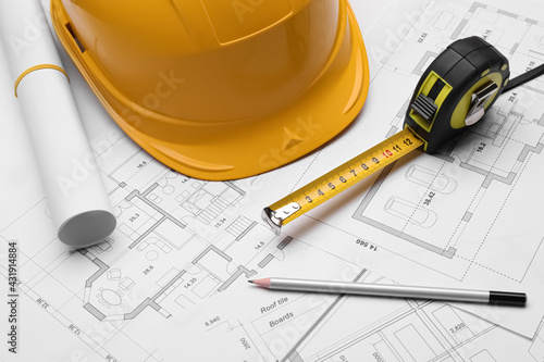 Pencil, measuring tape and hardhat on blueprints