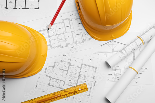 Flat lay composition with blueprints and hardhats on white background