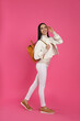 Leinwandbild Motiv Young woman with stylish backpack on pink background