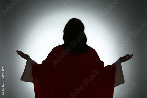 Fototapeta Silhouette of Jesus Christ with outstretched arms on color background, back view