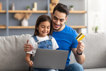 Family Using Computer And Credit Card At Home