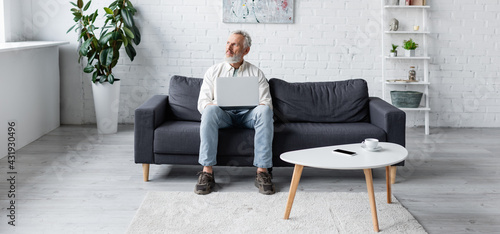 Obraz bearded man using laptop while sitting on couch near cup of coffee and smartphone with blank screen on coffee table, banner. - fototapety do salonu